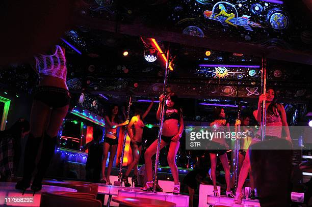 STORY 'EntertainmentUSThailandfilmFOCUS' by Janesara Fugal This picture taken on June 22 2011 shows bar girls dancing at a gogo bar in Bangkok's...