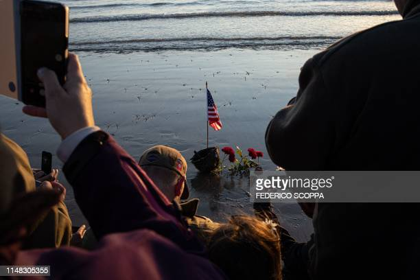 TOPSHOT WWII enthousiasts take pictures of an US flag and soldier helmet on Omaha beach near CollevillesurMer Normandy northwestern France in the...