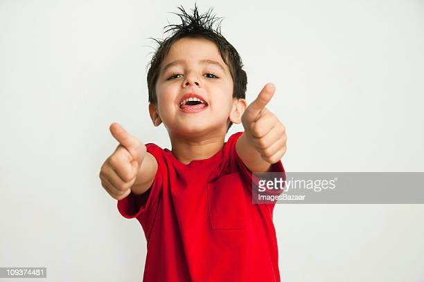 Enthusiastic boy (4-5) with thumbs-up