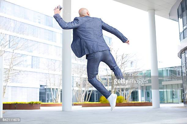 Enthusiastic businessman listening to music from smartphone and jumping mid-air