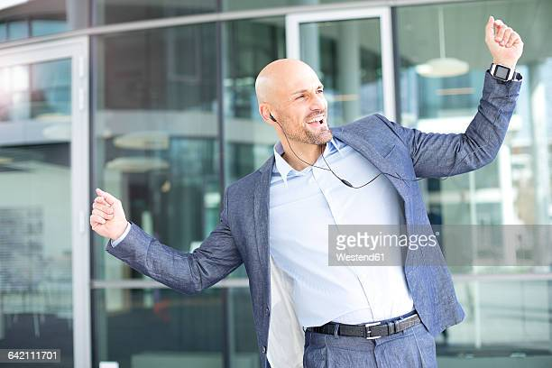 Enthusiastic businessman listening to music from smartwatch