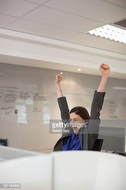 Enthousiaste Femme d'affaires avec les bras dans le bureau