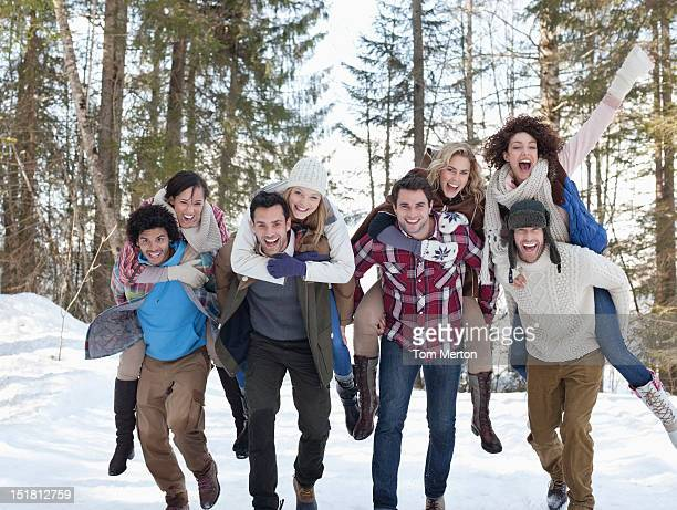 enthusiastic couples piggybacking in snowy woods - medium group of people stock pictures, royalty-free photos & images