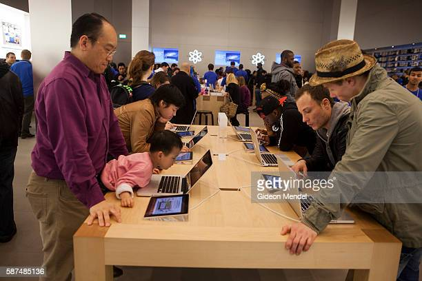 Enthusiastic customera try out Apple computer products at the Apple Store in new Westfield Stratford City mall which has seen huge crowds of...
