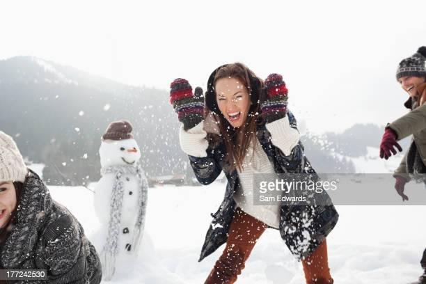 Entusiasta amigos disfrutando de bola de nieve lucha en el campo