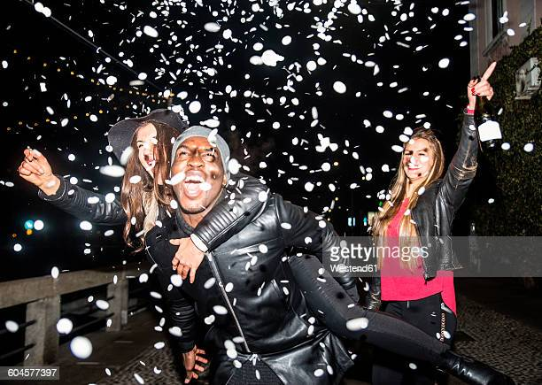 enthusiastic friends having a party outdoors at night - piggyback stock photos and pictures