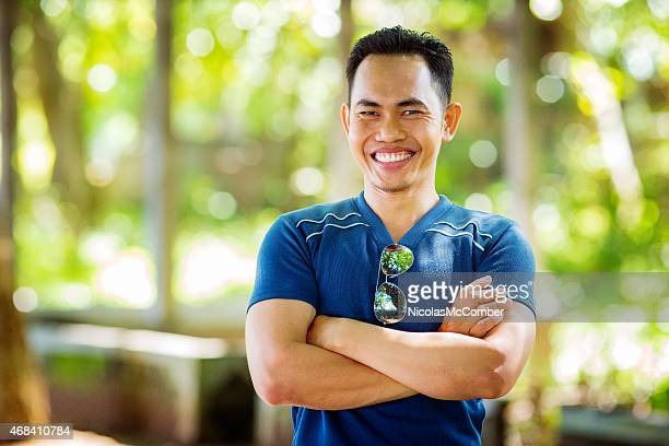 Enthusiastic mid-adult Indonesian man smiling arms crossed outdoors