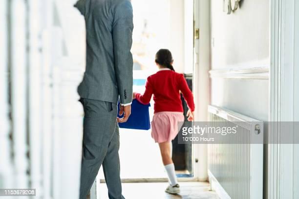 enthusiastic schoolgirl running through open doorway in morning - écolière photos et images de collection