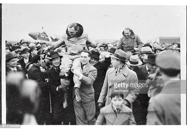 Enthusiastic spectators at Brussels Airport are pictured as they hoisted Ken Waller British flier and Captain Franchomme Belgian ace to their...