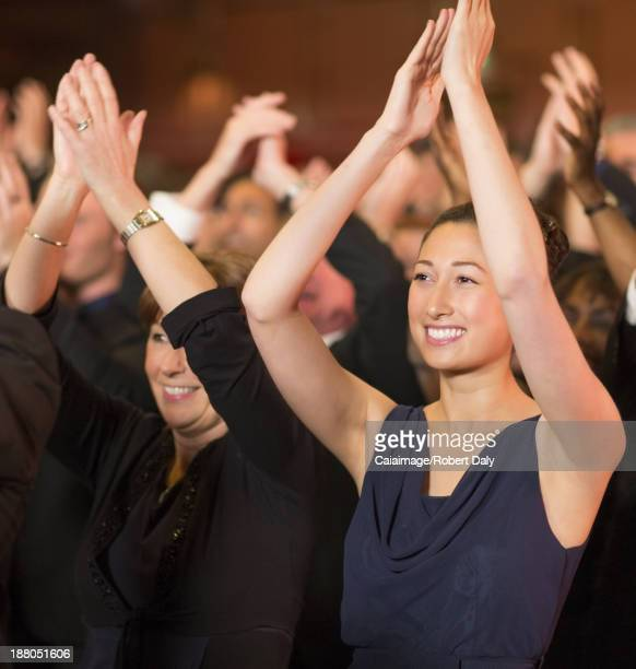 Enthousiaste femme Taper dans les mains en public de théâtre