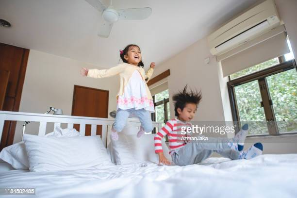 enthusiastic young chinese brother and sister jumping on bed - girl wrestling stock pictures, royalty-free photos & images