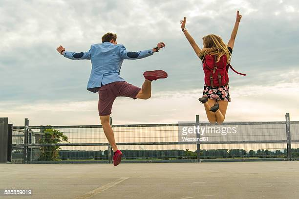 Enthusiastic young couple jumping on parking level