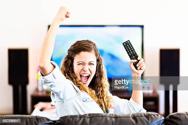 Enthusiastische junge weibliche Zuschauer wird von Fernseher jubeln eine Zeitlang triumphierend