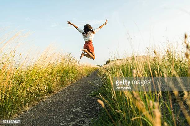 enthusiastic young woman jumping on path in field - hochspringen stock-fotos und bilder