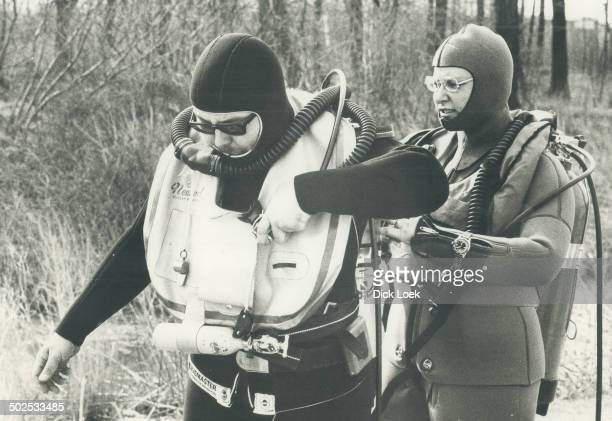 Enthusiasts in one of Ontario's most popular and fastest growing sports scuba diving attach air tanks and check over mouth pieces before setting out...