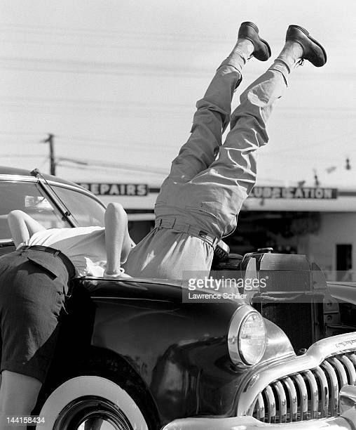 Entitled 'Head over Heels in Work' picture shows two people at work on a car engine one of them nearly vertically upside down his upper torso hidden...