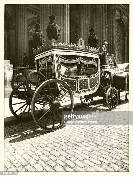 Entitled 'Pompe Funebre ' image shows an orante openair horsedrawn hearse parked in front of a large unidentifed building probably in Paris France...