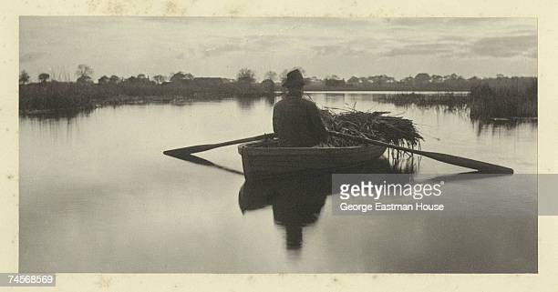 Entitled 'Rowing Home the SchoofStuff' the image shows a man as he rows a skiff with bundles of reeds on a river England mid 1880s The images was...