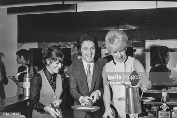 Entouré par Jacqueline Huet et par Anne-Marie Peysson, David Alexandre Winter s'essaie à faire des crèpes au Drugstore-Opéra, à Paris, France le 4...