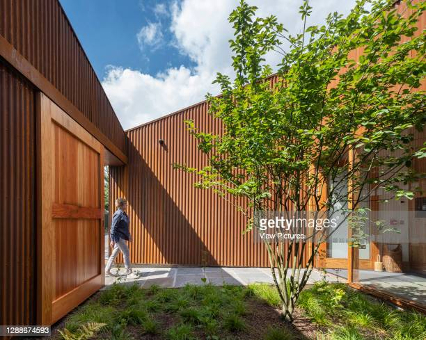 Entrance and garden courtyard. Maggie's Centre at Velindre Hospital, Cardiff, United Kingdom. Architect: Dow Jones Architects, 2019.