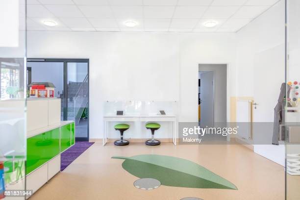 Entrance area at a doctors office or dentists office. Front desk and modern waiting area for children with tablets.