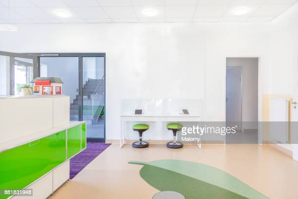 entrance area at a doctors office or dentists office. front desk and modern waiting area for children with tablets. - doctor's surgery stock pictures, royalty-free photos & images