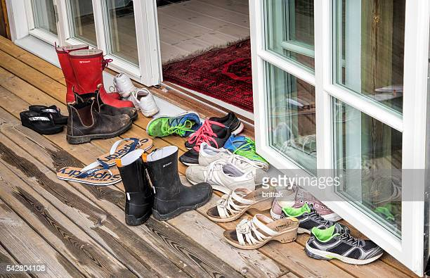 Entrance door in rainy weather with shoes and boots.