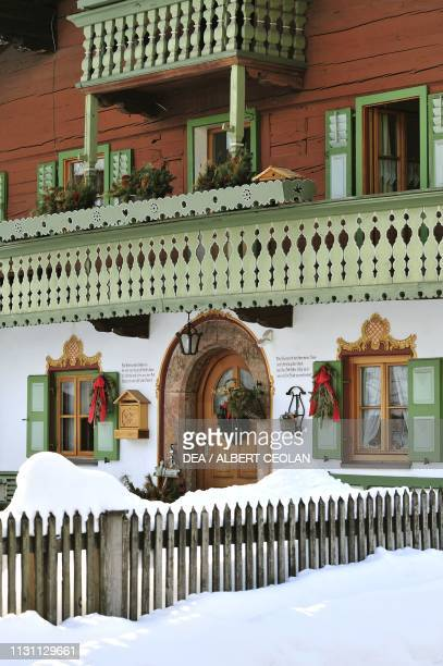 Entrance facade of a typical house in Reit im Winkl surrounded by snow Bavaria Germany