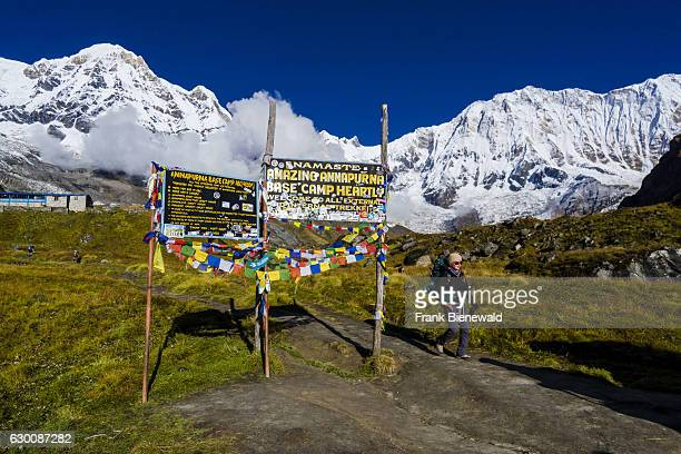 Entrance gate of Annapurna Base Camp with a walking trekker, the snow covered Annapurna 1 North Face and the Annapurna South summit .