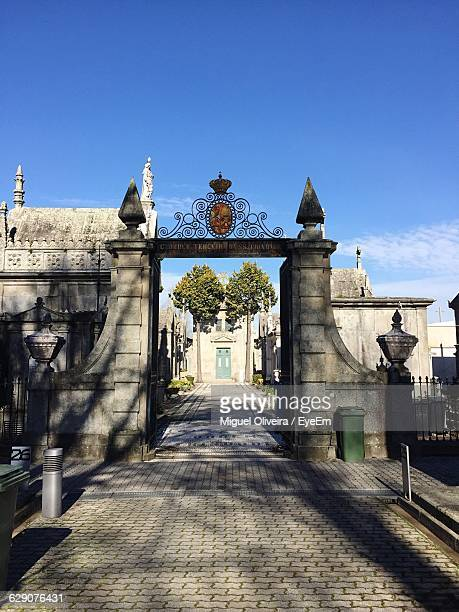 Entrance Gate Of Cemetery Against Clear Blue Sky