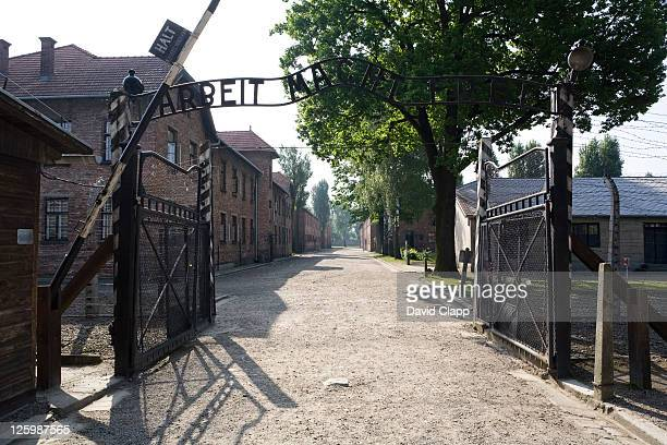 entrance gateway into auschwitz i, arbeit macht frei - 'work sets you free' at auschwitz concentration camp, poland - arbeit macht frei foto e immagini stock