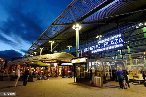 entrance of amsterdam airport schiphol in the evening - schiphol airport stock photos and pictures