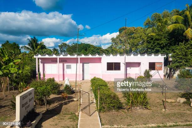 Entrance to a Cuban rural school The bare front yard of the pink building the fence door amid small bushes After the Cuban Revolution education...