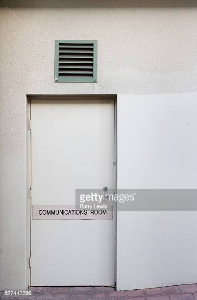 Entrance to a white office block in Manly Sydney with a makeshift 'Communications Room' sign on the door