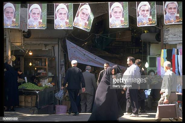 Entrance to bazaar w. Presidential election campaign posters picturing conservative cleric candidate Ali Akbar Nateq-Noori strung overhead & 1...