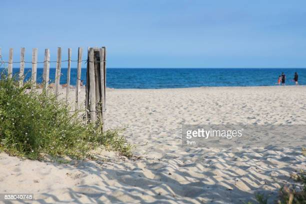 Entrance to the beach, with wooden fence to protect the dunes (Mediterranean sea, France)