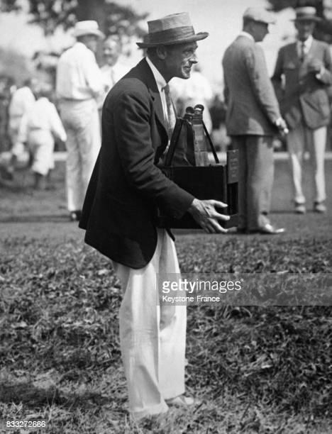Entraîneur de football américain Percy Haughton essayant dans son Country club un appareil photo portatif pour voir comment travaillent 'les...