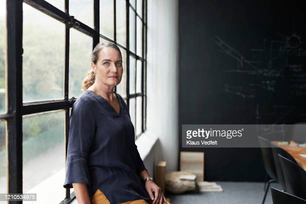 entrepreneur by window in board room at workplace - focus on foreground stock pictures, royalty-free photos & images