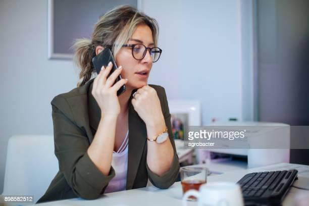 empreendedor, ligando no telefone trabalhando no escritório - attending - fotografias e filmes do acervo