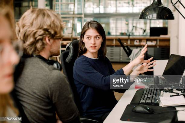 entrepreneur explaining to colleague while sitting in office - coding stock pictures, royalty-free photos & images