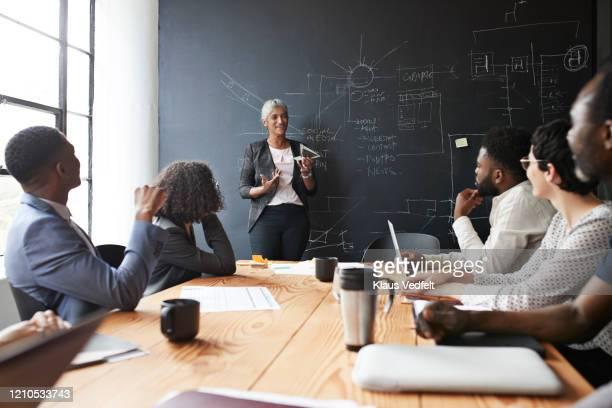 entrepreneur explaining to colleagues in meeting - coinvolgimento dei dipendenti foto e immagini stock