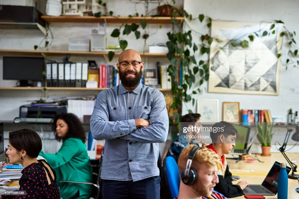 Entrepreneur in busy office smiling at camera : Stock Photo