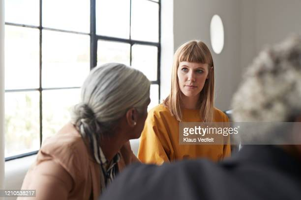 entrepreneur looking at coworker at workplace - mid adult stock pictures, royalty-free photos & images