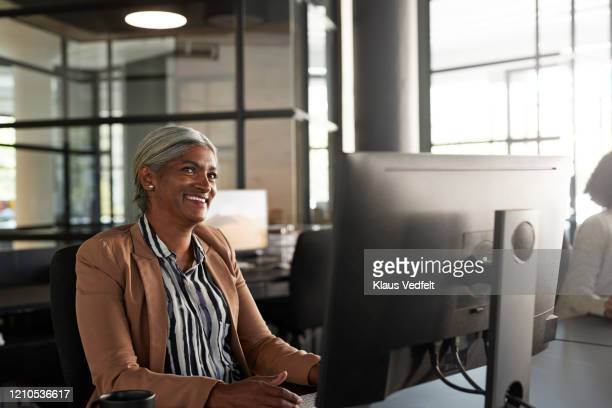 entrepreneur looking away at modern office desk - striped blazer stock pictures, royalty-free photos & images