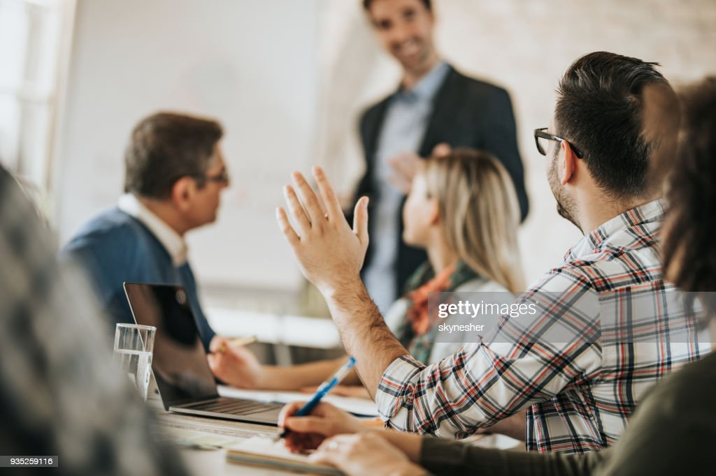 Entrepreneur raising his hand to ask a question on a business meeting in the office. : Stock Photo