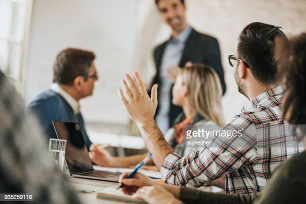 Entrepreneur raising his hand to ask a question on a business meeting in the office.