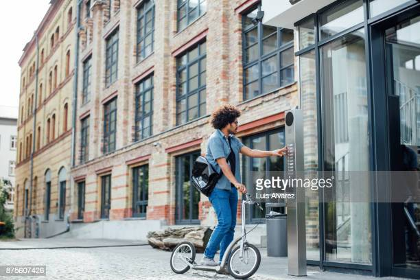 entrepreneur riding push scooter in city - intercom stock photos and pictures