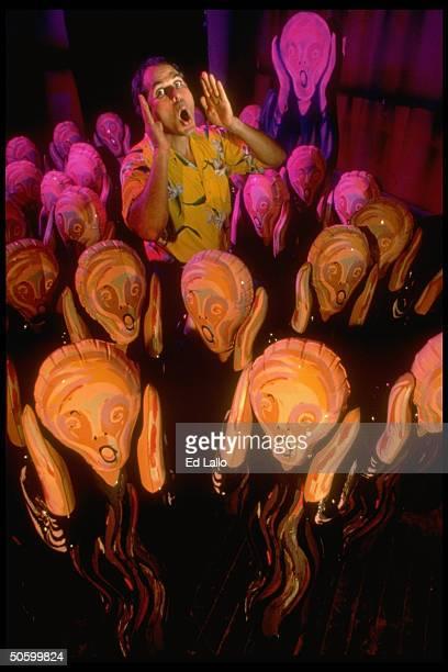 Entrepreneur Robert Fishbone screaming as he stands amid 18 or more Scream dolls 4 1/2ft simulacra of Norwegian artist Edvard Munch's The Scream