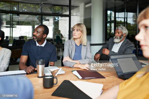 entrepreneur sitting by conference table in office - disabilitycollection stock pictures, royalty-free photos & images
