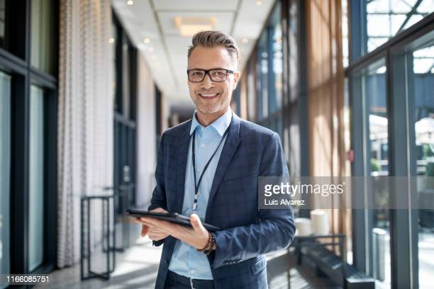 entrepreneur standing in hotel corridor - businessman stock pictures, royalty-free photos & images